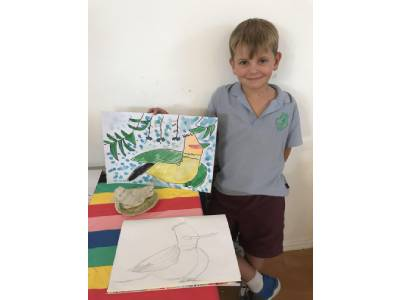 The boy stand with wear gray t shirt & drawn art of bird After school activities for kids